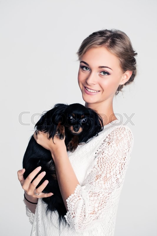 Stock image of 'Fashion Woman holding Small Dog'
