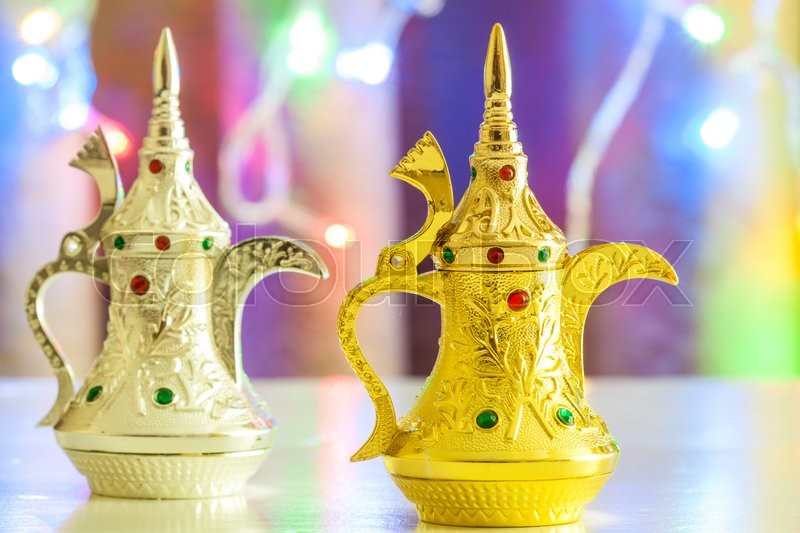 Stock image of 'Gold and Silver Arabic Coffee pots in colorful illuminated background. Ramadan and Eid concept background'
