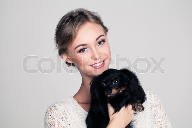 Stock image of 'Cute Woman with Dog in Her Hands'