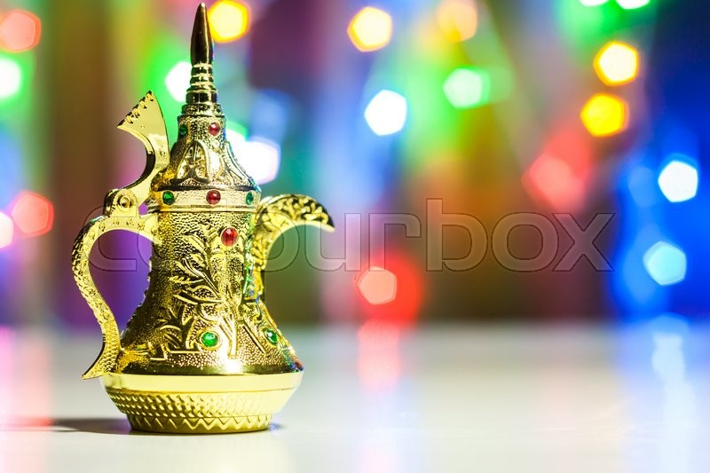 Stock image of 'Golden Arabic Coffee pots in colorful illuminated background. Ramadan and Eid concept background'