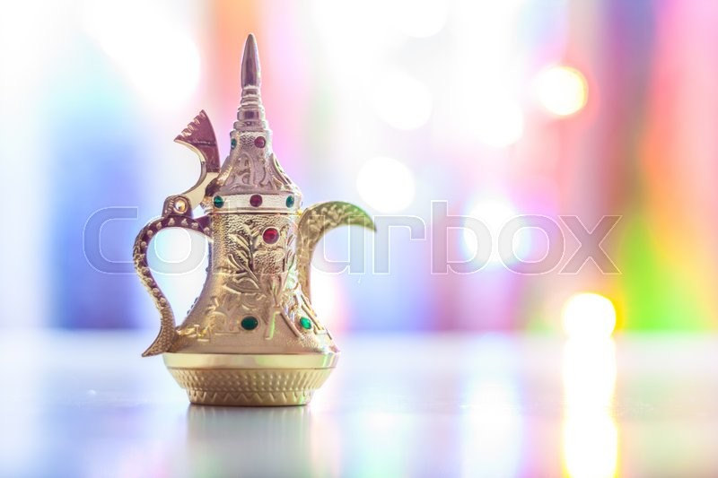 Stock image of 'Silver Arabic Coffee pots in colorful illuminated background. Ramadan and Eid concept background'