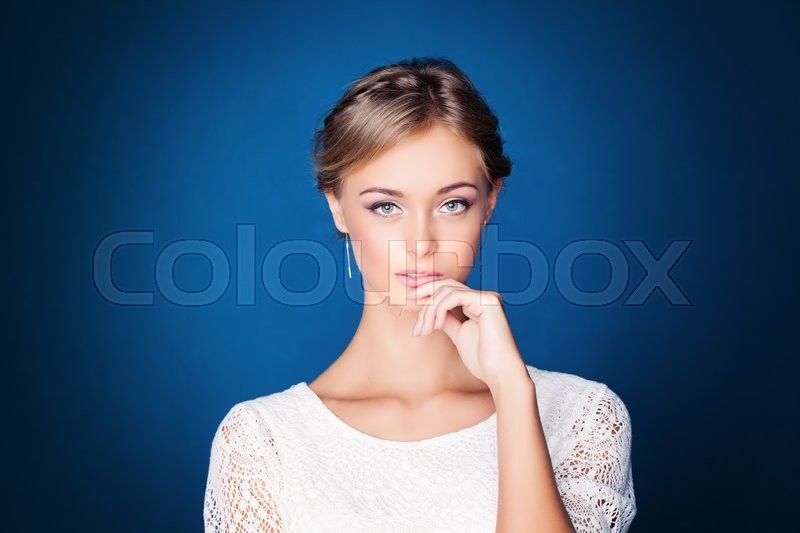 Stock image of 'Young Pensive Woman on Blue Background'