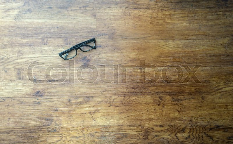 Stock image of 'black nerdy glasses on a wood floor'