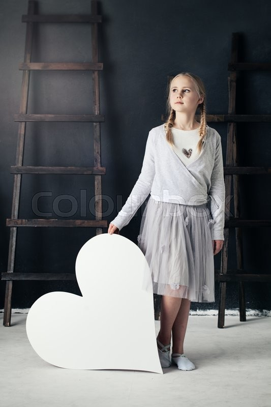 Stock image of 'Fashion Child Girl and Big White Heart. Fashion Portrait'