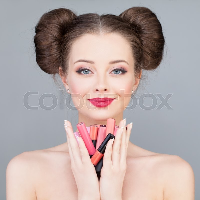 Stock image of 'Makeup. Pretty Girl Holding Bright Lipsticks and Lipgloss'