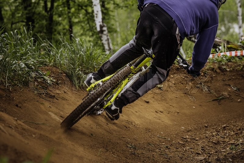 Stock image of 'male athlete mountain biker down from mountain through woods during a downhill competition'