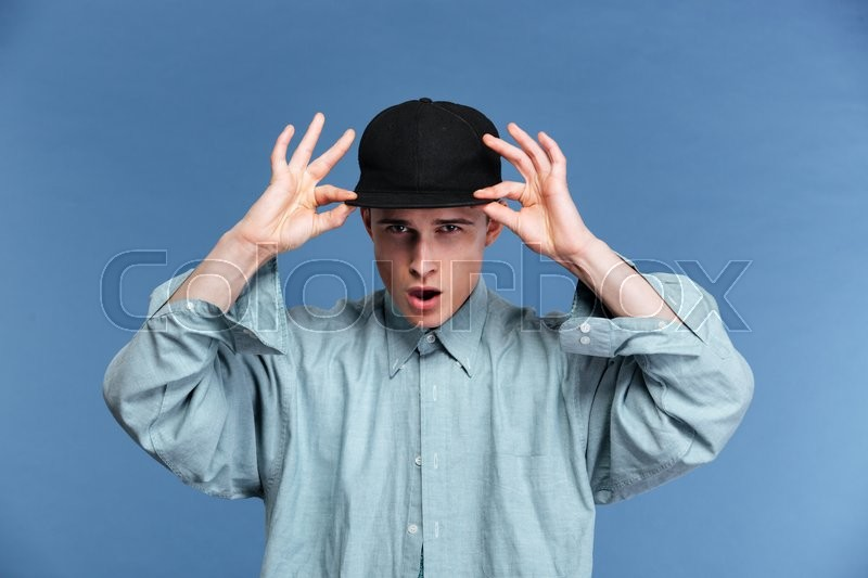 Stock image of 'Young teenager putting cap on and posing isolated on the blue background'