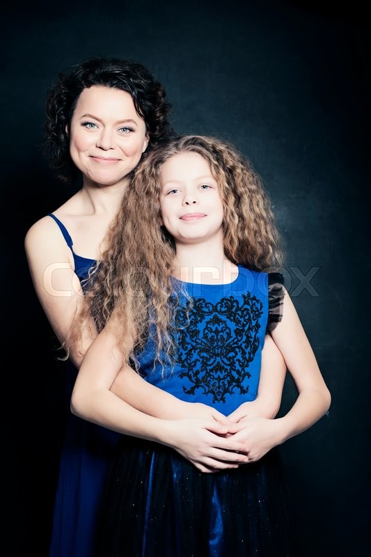 Stock image of 'Beautiful Mother and Daughter Embracing on Blue Background'