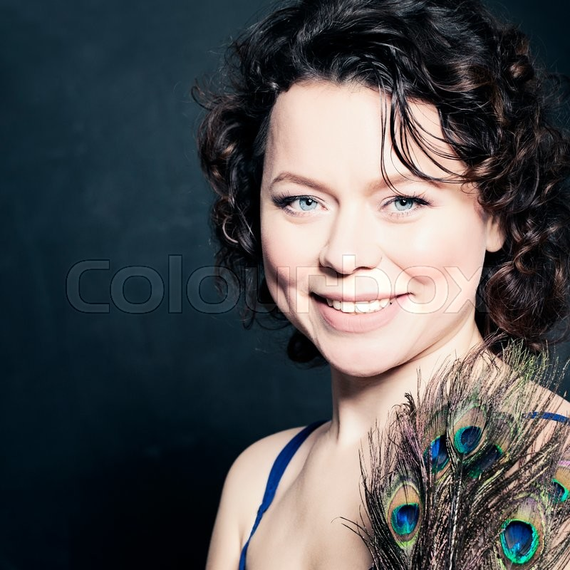 Stock image of 'Beautiful Mature Woman Fashion Brunette with Peacock Feathers'