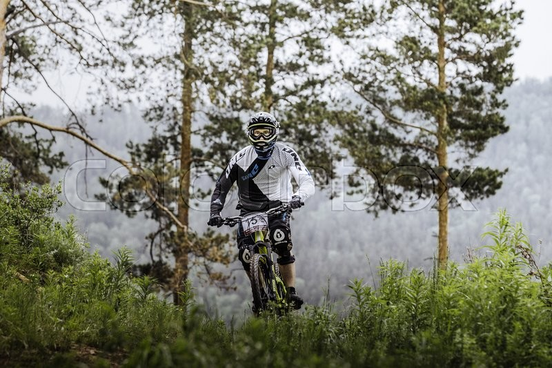 Editorial image of 'Miass, Russia - May 29, 2016: athlete mountainbiker in forest mountains in background during Cup \