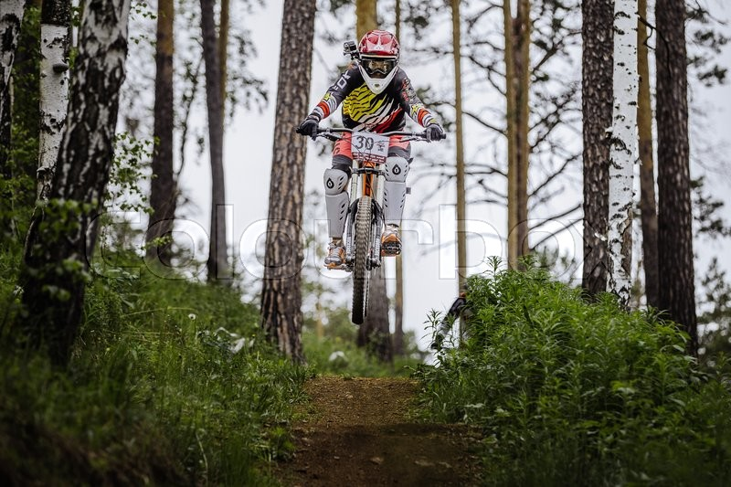 Editorial image of 'Miass, Russia - May 29, 2016: athlete racer bike jump with a mountain in forest on helmet video camera during Cup \
