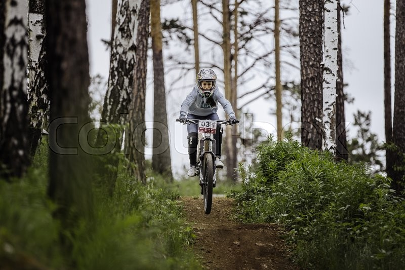 Editorial image of 'Miass, Russia - May 29, 2016: girl mountbike on bike rides on track in forest during Cup \