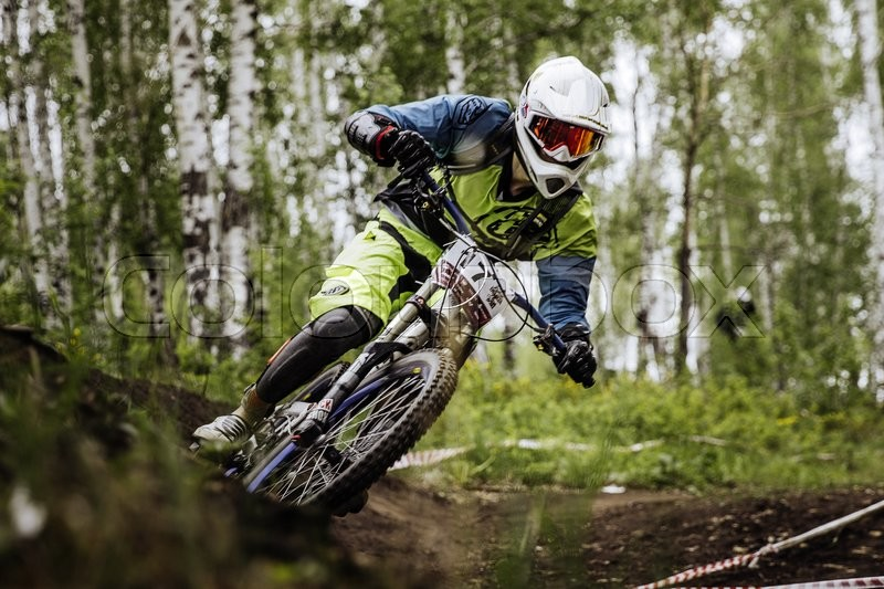 Editorial image of 'Miass, Russia - May 29, 2016: closeup man athlete mountain biking around sharp turn in forest during Cup \
