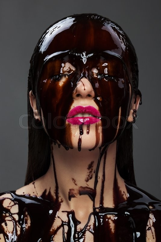 Stock image of 'beautiful young brunette woman chocolate flowing down her face, her eyes closed and her lips pink'