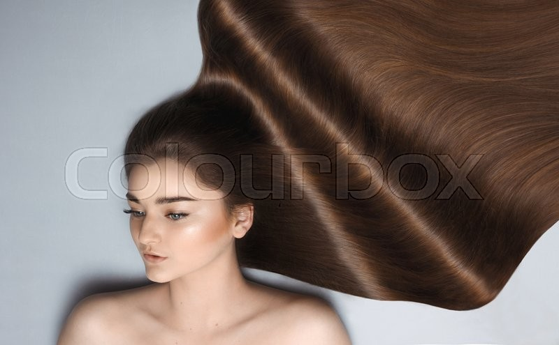 Stock image of 'beauty close-up portrait of beautiful female face with long dark waved hairs laying down'