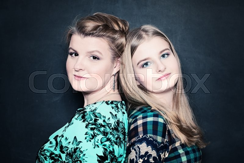Mother and Daughter. Real People. Mature Woman and Girl on Black Background, stock photo