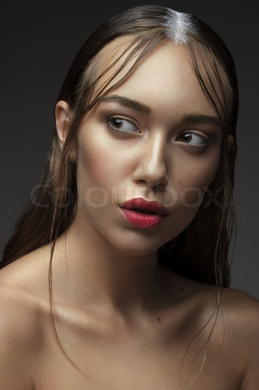 Stock image of 'Beautiful Young Woman with Clean Fresh Skin. Close up Portrait. Fashion Model Girl Face. Perfect Skin. Professional Makeup. Fashion shiny highlighter on skin, sexy gloss lips. '