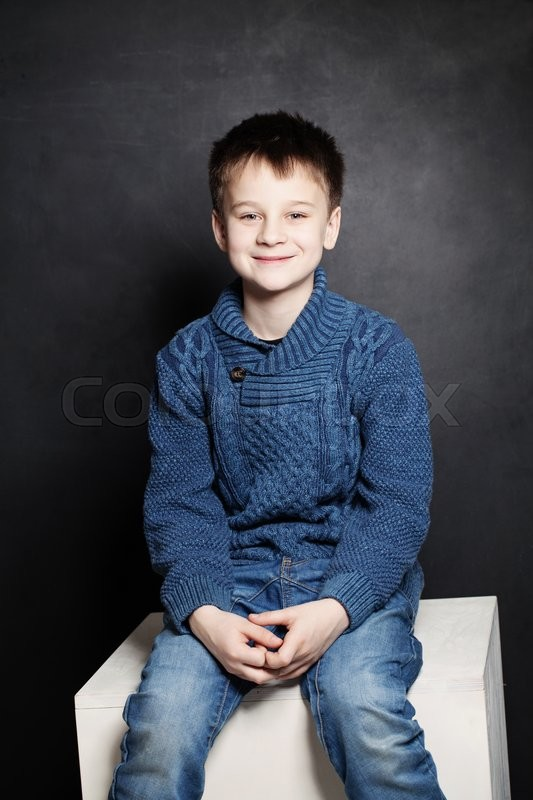 Stock image of 'Smiling Child Boy in Blue Sweater on Dark Background'