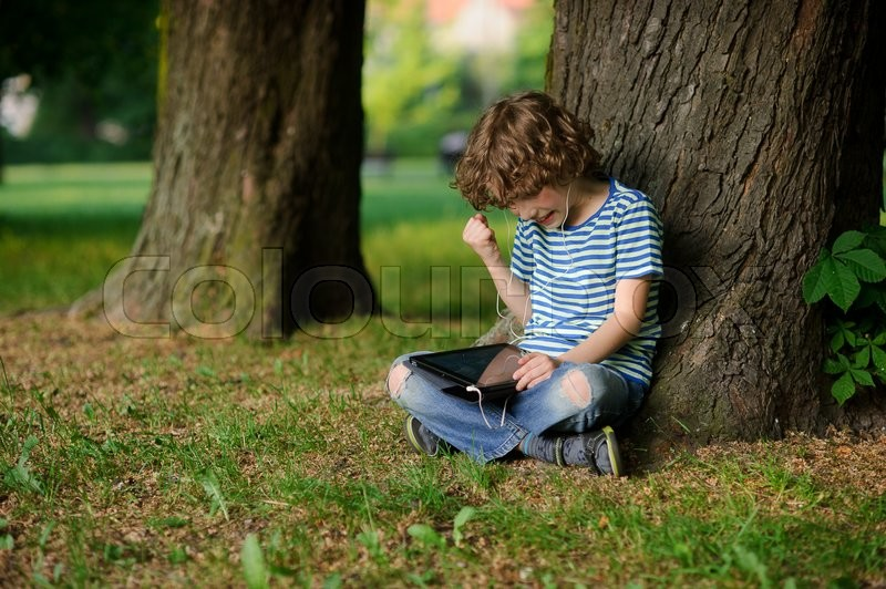 Stock image of 'The boy is keen on game on the tablet. He has raised a hand with the clenched fist. The person is strained. Behind the back of the boy a trunk of an old tree. Jeans full of holes.'