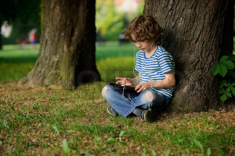 Stock image of 'The boy of 8-9 years sits under a big tree with the tablet on a lap. He thoughtfully looks at the tablet screen. In ears earphones. Jeans are on a lap torn.'