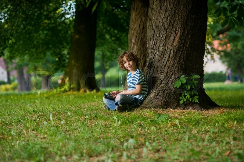 Stock image of 'The boy with the tablet on a lap. He sits in park under a big old tree. In ears earphones. Thoughtful face. The boy looks in a camera.'