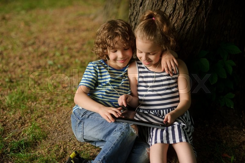 Stock image of 'Two children sit under more tree with interest looking at the tablet screen. The boy and the girl sit having embraced. They smile, having inclined over the tablet.'