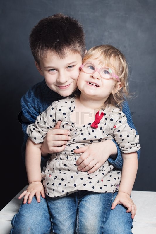 Stock image of 'Smiling Little Girl and Boy Sibling. 2 and 10 years'