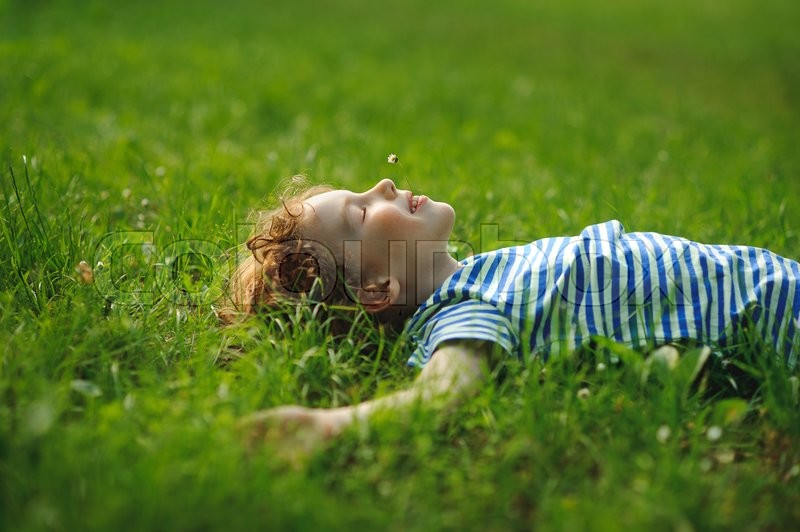 Stock image of 'The boy of 8-9 years lies in the field on a green grass. He has stretched hands in the parties. In a mouth a floret. Eyes are closed from pleasure. Blond curly hair. On cheeks a flush.'