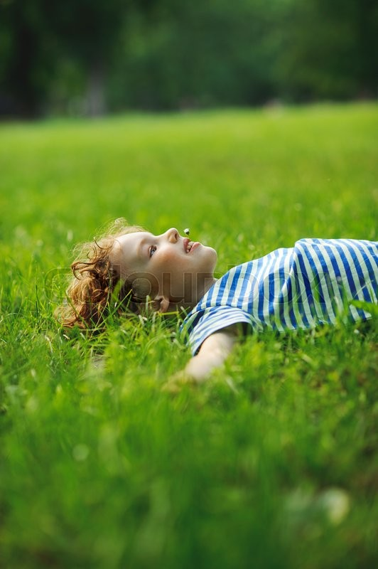 Stock image of 'The little boy lies on a green lawn in park. He has stretched hands in the parties. In a mouth a floret. Eyes pensively look up. Blond curly hair. On cheeks a flush.'