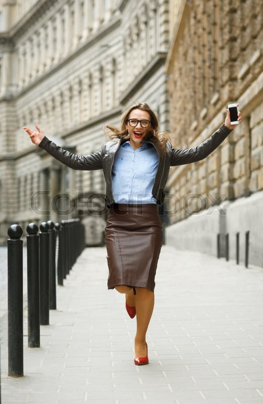 Stock image of 'Delighted business woman jumping for joy while talking on the smart phone on the street'