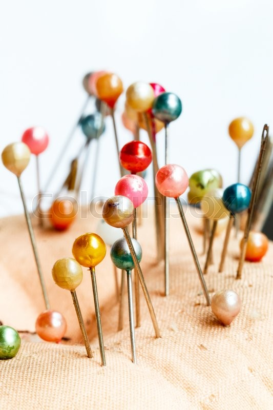 Stock image of 'Fabric pincushion with colorful pins on white background'