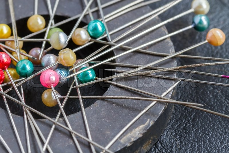 Stock image of 'Pins attach round magnetic pincushion on black leather background'