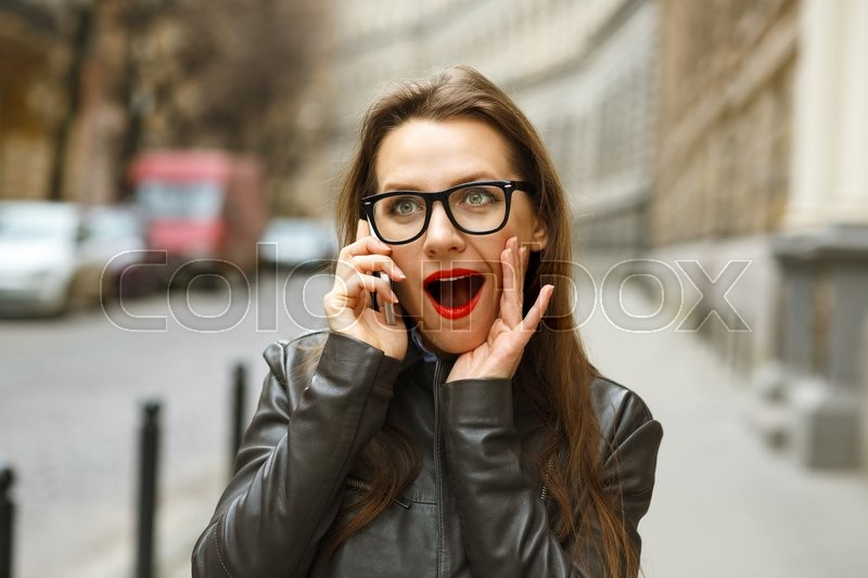 Stock image of 'Surprised businesswoman walking down the street while talking on smart phone'