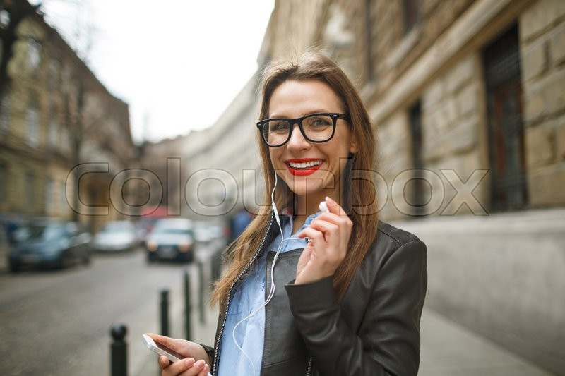 Stock image of 'Businesswoman walking down the street while talking on smart phone. Happy smiling caucasian business woman busy'