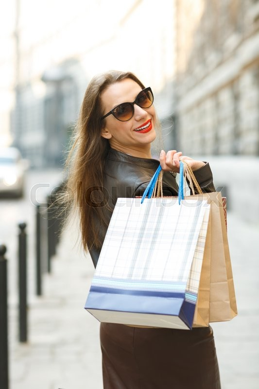 Stock image of 'Sale, shopping, tourism and happy people concept - beautiful woman with shopping bags in the ctiy'