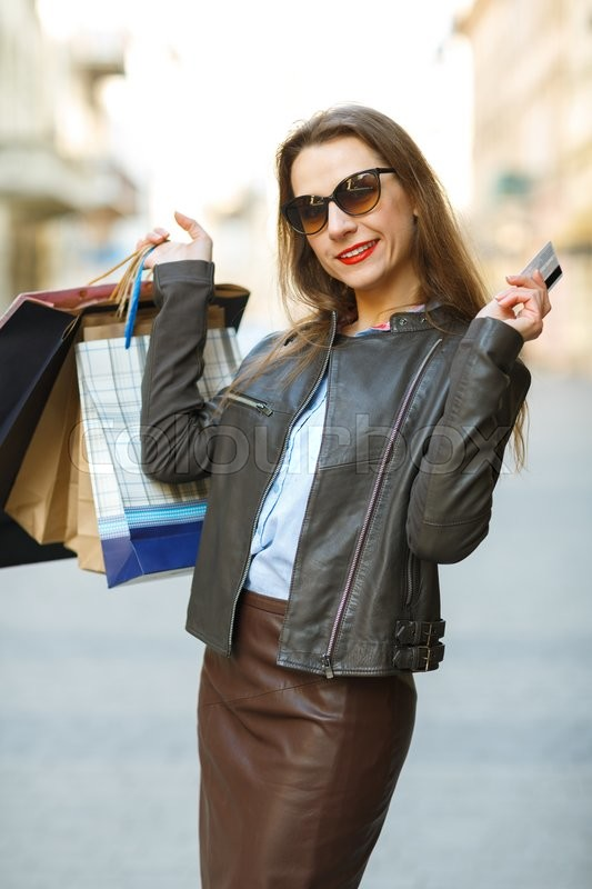 Stock image of 'Sale, shopping, tourism and happy people concept - beautiful woman with shopping bags and credit card in the hands on a street'