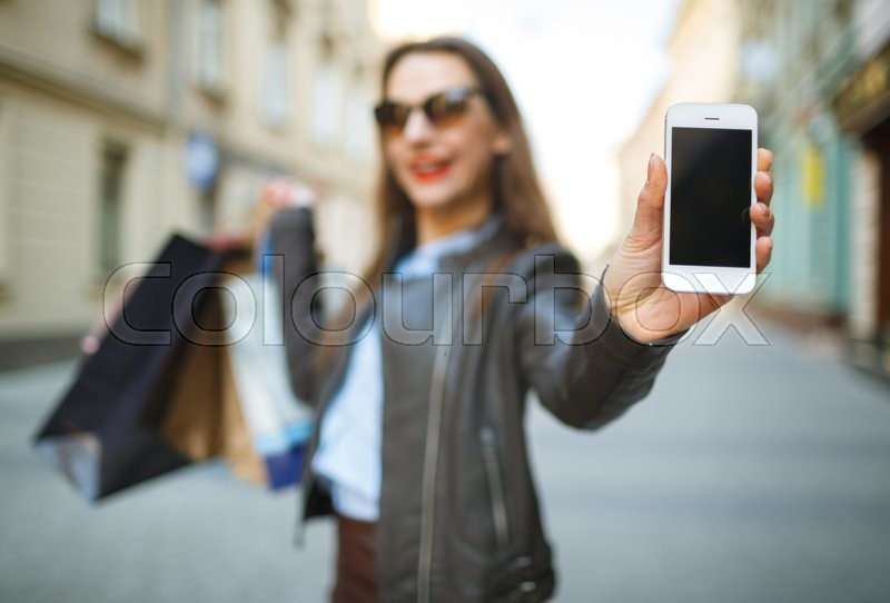 Stock image of 'Online shopping concept - beautiful woman with shopping bags and smart phone in the hands on a street'