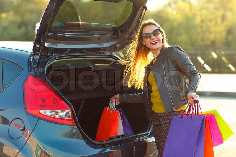 Stock image of 'Smiling Caucasian woman putting her shopping bags into the car trunk'