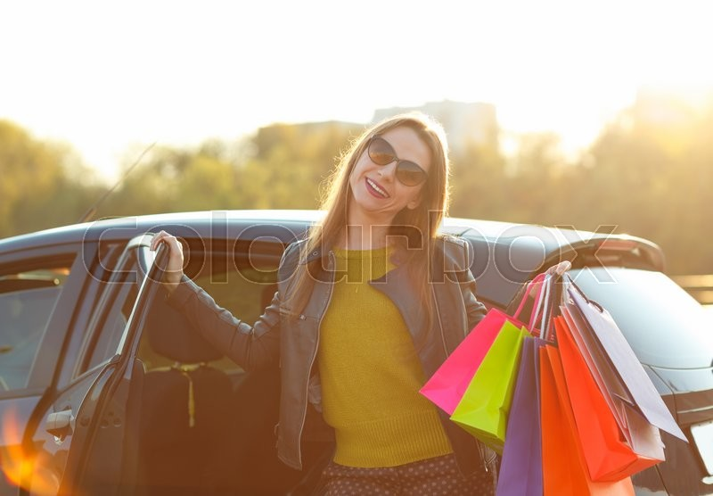 Stock image of 'Smiling Caucasian woman putting her shopping bags into the car - shopping concept'