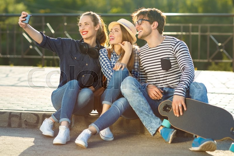 Stock image of 'Friendship, leisure, summer, technology and people concept - smiling friends making selfie outdoors'