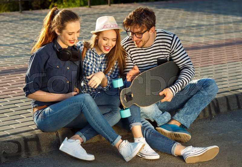Stock image of 'Friendship, leisure, summer, technology and people concept - smiling friends having fun outdoors'