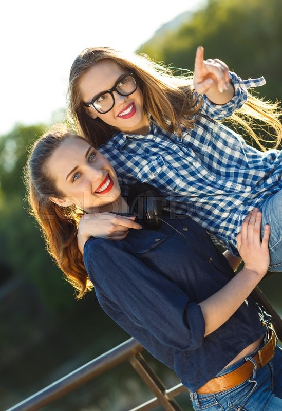 Stock image of 'Two playful young women having fun outdoors at sunset light'