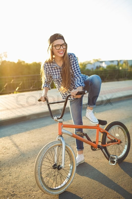 Stock image of 'Lovely young woman in a hat riding a bicycle on city background in the sunlight outdoor. Active people'
