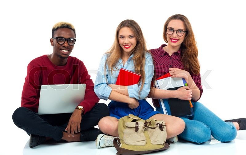 Stock image of 'Three happy young teenager students sitting with books, laptop and bags isolated on white background'