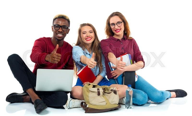 Stock image of 'Three happy young teenager students with books, laptop and bags with thumbs up isolated on white background'