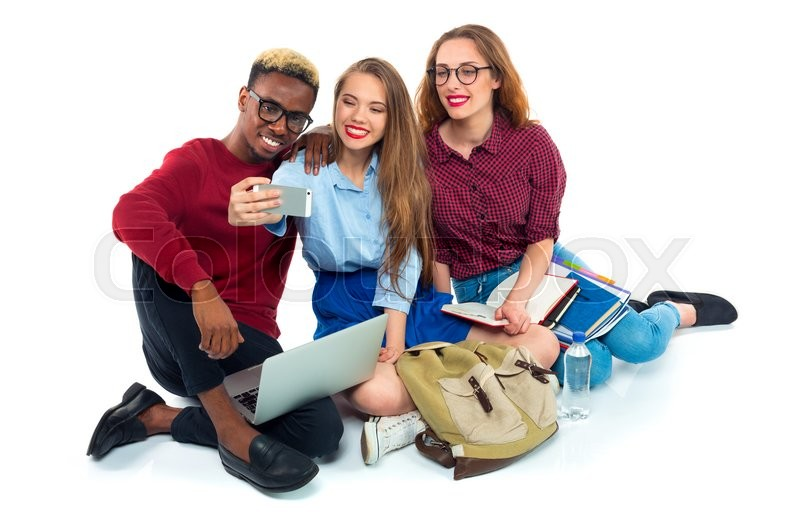 Stock image of 'Three happy young teenager students with books, laptop, bags and makes selfie on white background'