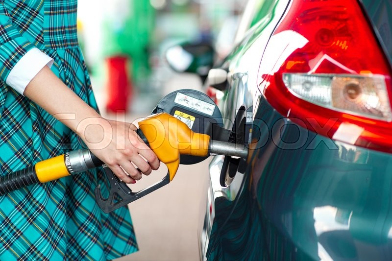 Stock image of 'Woman fills petrol into the car at a gas station'
