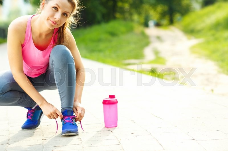 Stock image of 'Closeup shot of young woman tying shoelaces before running'