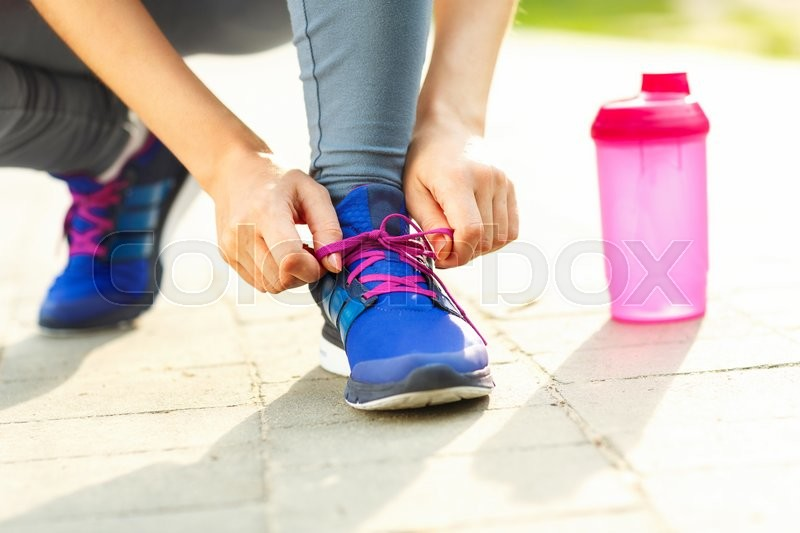 Stock image of 'Running shoes - woman tying shoe laces. Closeup of female sport fitness runner getting ready for jogging outdoors in summer'