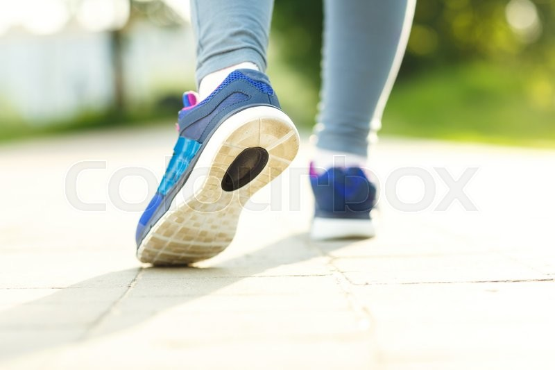 Stock image of 'Running shoes - closeup of female sport fitness runner getting ready for jogging outdoors in summer'